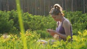 Mujer joven feliz que se sienta en smartphone verde del césped y de las aplicaciones en campo escénico en el fondo de la puesta d metrajes
