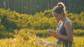 Mujer joven feliz que se sienta en smartphone verde del césped y de las aplicaciones en campo escénico en el fondo de la puesta d almacen de metraje de vídeo