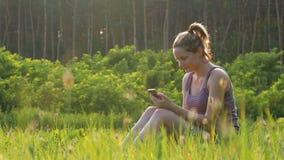 Mujer joven feliz que se sienta en smartphone verde del césped y de las aplicaciones en campo escénico en el fondo de la puesta d almacen de video