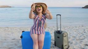 Mujer joven feliz que se sienta en una maleta que muestra los pulgares para arriba almacen de video