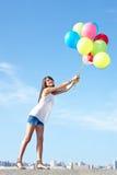 Mujer joven feliz que se va volando con los globos Imagen de archivo libre de regalías