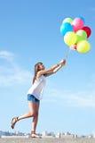 Mujer joven feliz que se va volando con los globos Foto de archivo