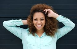 Mujer joven feliz que sonríe al aire libre contra fondo negro Foto de archivo libre de regalías