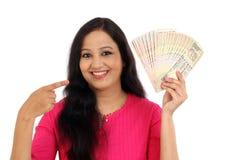 Mujer joven feliz que sostiene billetes de banco de la rupia india Foto de archivo libre de regalías