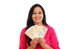 Mujer joven feliz que sostiene billetes de banco de la rupia india Fotografía de archivo libre de regalías