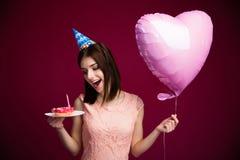 Mujer joven feliz que sostiene el buñuelo con la vela Fotos de archivo libres de regalías