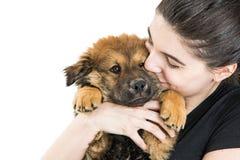 Mujer joven feliz que sostiene el perrito en blanco Fotografía de archivo libre de regalías