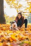 Mujer joven feliz que sostiene el perro alegre al aire libre Imagenes de archivo
