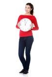 Mujer joven feliz que sostiene el reloj de la oficina Fotos de archivo
