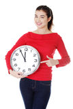 Mujer joven feliz que sostiene el reloj de la oficina Fotografía de archivo libre de regalías