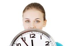 Mujer joven feliz que sostiene el reloj de la oficina Foto de archivo libre de regalías