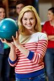 Mujer joven feliz que sostiene la bola en club de los bolos Imagenes de archivo