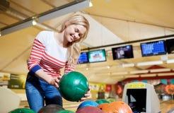 Mujer joven feliz que sostiene la bola en club de los bolos Imagen de archivo