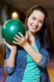 Mujer joven feliz que sostiene la bola en club de los bolos Fotografía de archivo