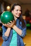Mujer joven feliz que sostiene la bola en club de los bolos Foto de archivo