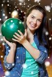 Mujer joven feliz que sostiene la bola en club de los bolos Fotos de archivo libres de regalías
