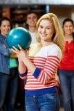 Mujer joven feliz que sostiene la bola en club de los bolos Imagen de archivo libre de regalías