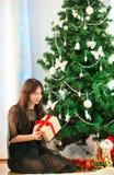 Mujer joven feliz que sostiene la caja del regalo de Navidad el Nochebuena Foto de archivo libre de regalías