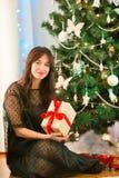 Mujer joven feliz que sostiene la caja del regalo de Navidad el Nochebuena Fotos de archivo libres de regalías