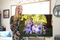 Mujer joven feliz que sostiene la impresión de la lona del retrato de la familia foto de archivo libre de regalías