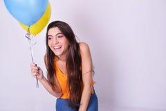 Mujer joven feliz que sostiene los globos coloridos Fotografía de archivo libre de regalías