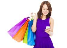 Mujer joven feliz que sostiene los panieres y el teléfono móvil imágenes de archivo libres de regalías