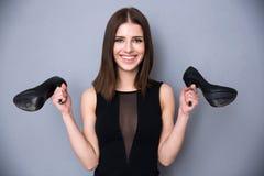 Mujer joven feliz que sostiene los zapatos Fotografía de archivo