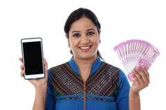 Mujer joven feliz que sostiene moneda india y el teléfono móvil Fotografía de archivo libre de regalías