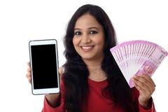 Mujer joven feliz que sostiene moneda india y el teléfono móvil Fotografía de archivo