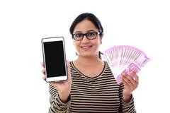 Mujer joven feliz que sostiene moneda india y el teléfono móvil Imagen de archivo
