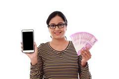 Mujer joven feliz que sostiene moneda india y el teléfono móvil Imágenes de archivo libres de regalías
