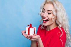 Mujer joven feliz que sostiene un regalo en sus manos Foto de archivo