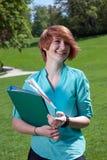 Mujer joven feliz que sostiene una carpeta de archivos al aire libre Fotos de archivo