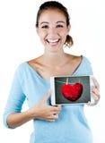 Mujer joven feliz que sostiene una tableta digital con un corazón en el s Fotos de archivo