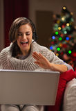 Mujer joven feliz que tiene charla video con la familia Foto de archivo