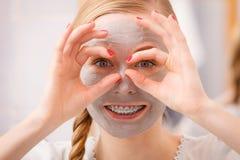Mujer joven feliz que tiene máscara del fango en cara Foto de archivo libre de regalías