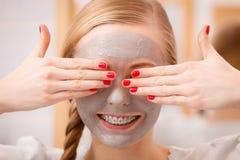 Mujer joven feliz que tiene máscara del fango en cara Imagen de archivo libre de regalías