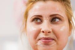 Mujer joven feliz que tiene máscara del gel en cara Fotografía de archivo libre de regalías
