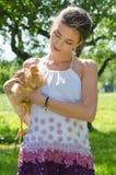 Mujer joven feliz que toma el cuidado del pollo Fotografía de archivo libre de regalías