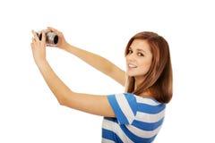 Mujer joven feliz que toma el selfie con la cámara clásica del slr Imagen de archivo libre de regalías