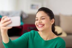 Mujer joven feliz que toma el selfie con smartphone Imagen de archivo libre de regalías