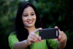 Mujer joven feliz que toma el selfie en al aire libre Imágenes de archivo libres de regalías