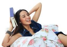 Mujer joven feliz que toma una siesta en casa con un libro Imágenes de archivo libres de regalías