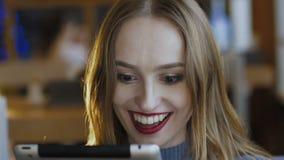 Mujer joven feliz que trabaja con la tableta y que sonríe en café lentamente almacen de video