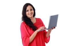 Mujer joven feliz que trabaja con un ordenador portátil foto de archivo