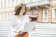 Mujer joven feliz que trabaja con un ordenador portátil que se sienta en un banco Foto de archivo