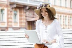 Mujer joven feliz que trabaja con un ordenador portátil que se sienta en un banco Imagen de archivo libre de regalías