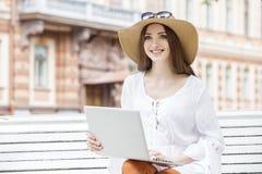 Mujer joven feliz que trabaja con un ordenador portátil que se sienta en un banco Fotografía de archivo libre de regalías