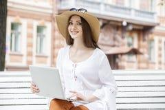 Mujer joven feliz que trabaja con un ordenador portátil que se sienta en un banco Imágenes de archivo libres de regalías
