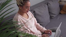 Mujer joven feliz que trabaja en el ordenador portátil en el sofá cómodo en casa almacen de video